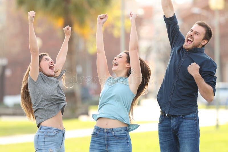3 blije vrienden die het vieren succes in een park springen royalty-vrije stock foto's