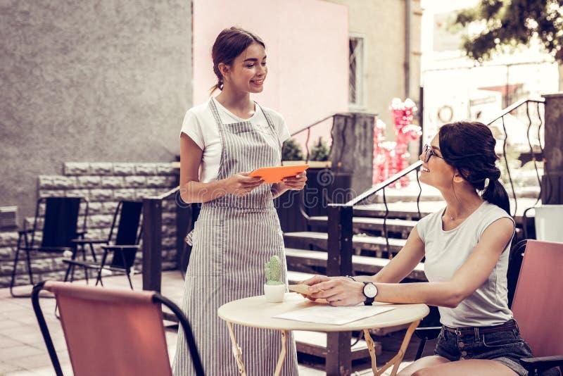 Blije vriendschappelijke serveerster die de orde van haar klant nemen stock foto