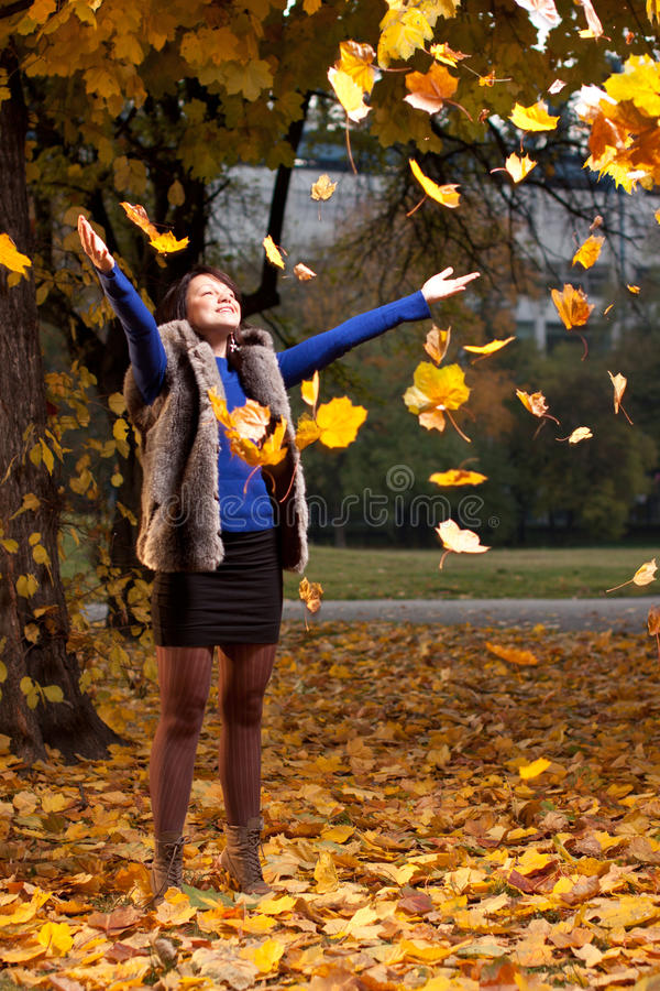 Blije vrouw die de herfstbladeren werpt stock foto