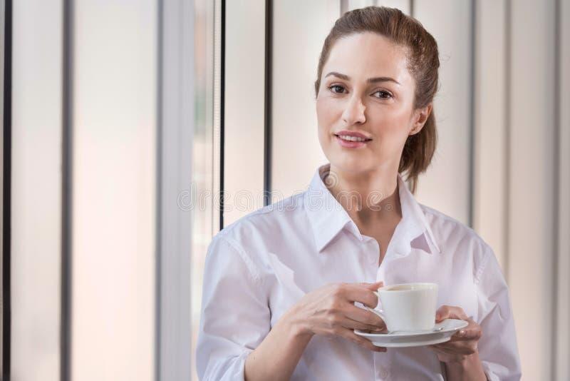 Blije vrouw die van koffiepauze in comfortabel bureau genieten stock fotografie