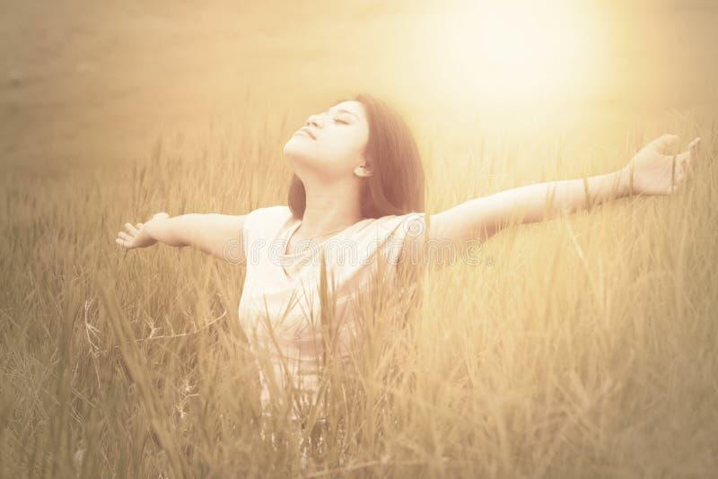 Blije vrouw die van verse lucht op weide genieten stock afbeeldingen