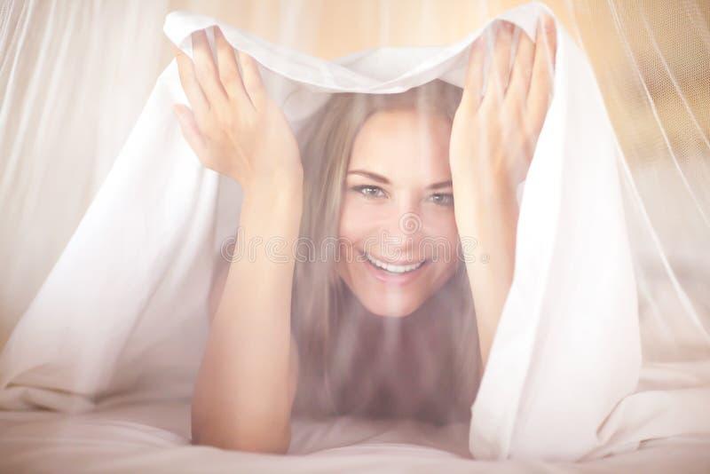 Blije vrouw in het bed stock fotografie