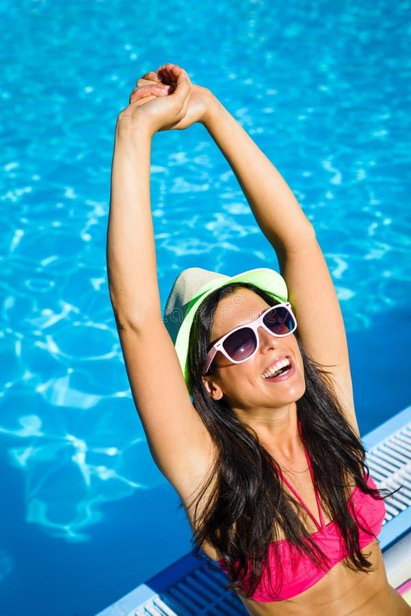 Blije vrouw op de zomervakantie bij zwembad stock foto