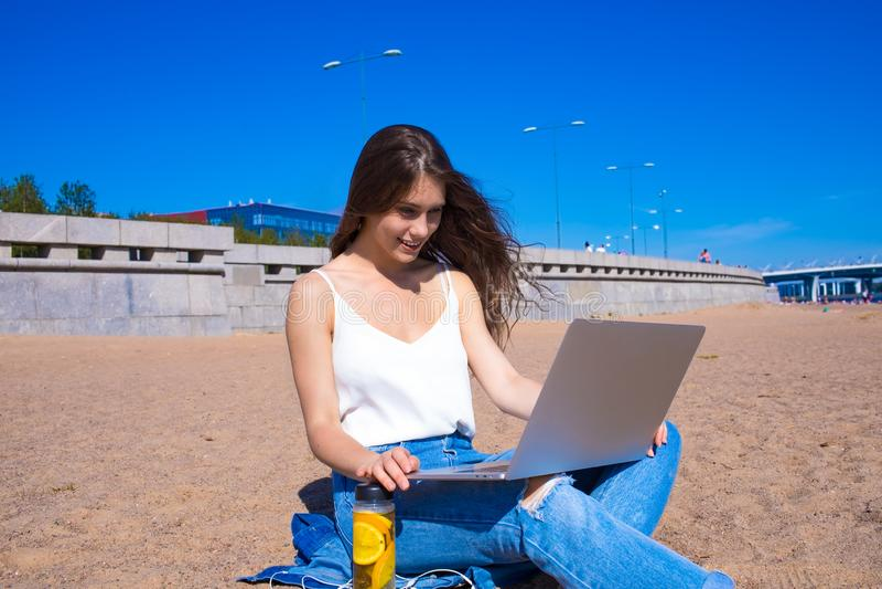 Blije vrouwelijke tekstschrijver het werk afstand op netbook, die in openlucht ontspannen royalty-vrije stock foto's