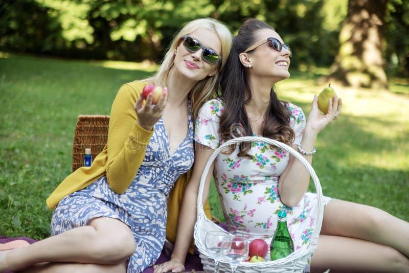 Blije vrouwen die sappig fruit eten stock foto
