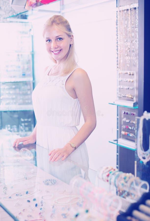 Blije vrouwenverkoper die zich naast glasshowcase bevinden stock foto's