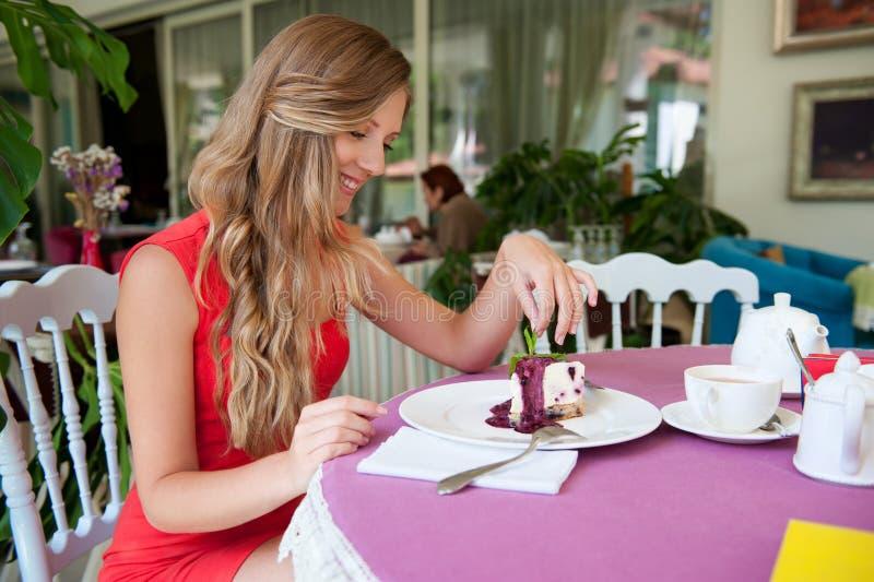 Blije vrouwenzitting in de koffie stock afbeelding