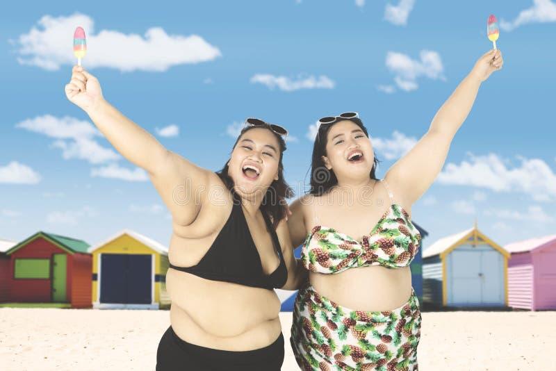 Blije zwaarlijvige vrouwen bij kust royalty-vrije stock fotografie