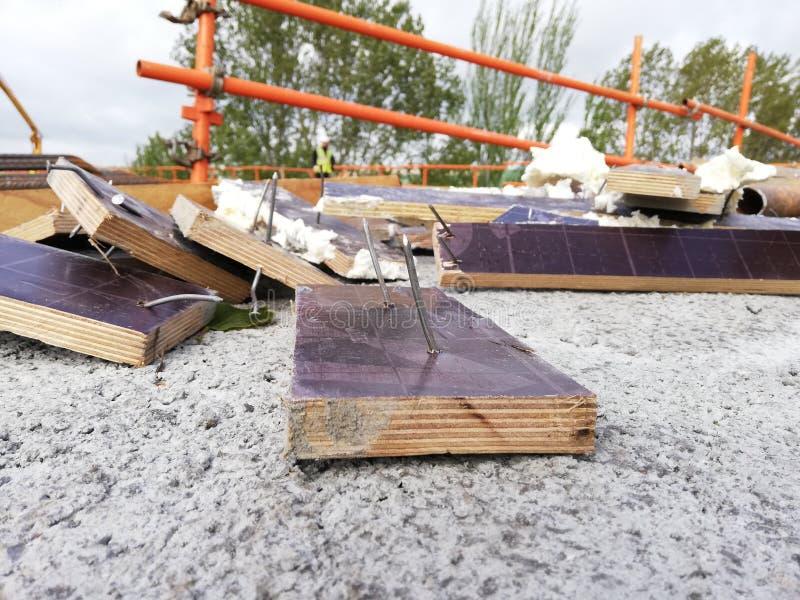 Blijft van puin op een plaats met spijkers wordt geworpen die een gevaar voor arbeiders die opleveren royalty-vrije stock fotografie