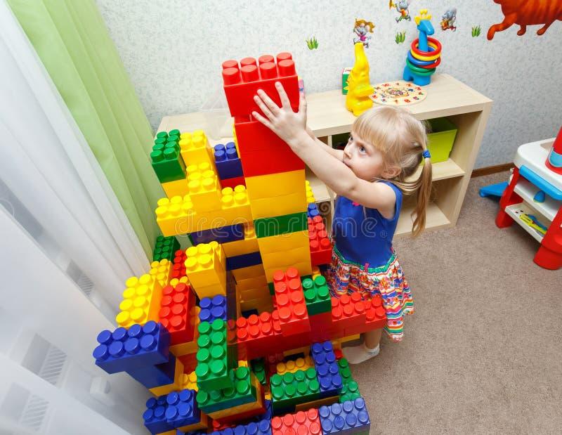 Blijvend meisje die grote bloktoren in opvang bouwen stock afbeeldingen