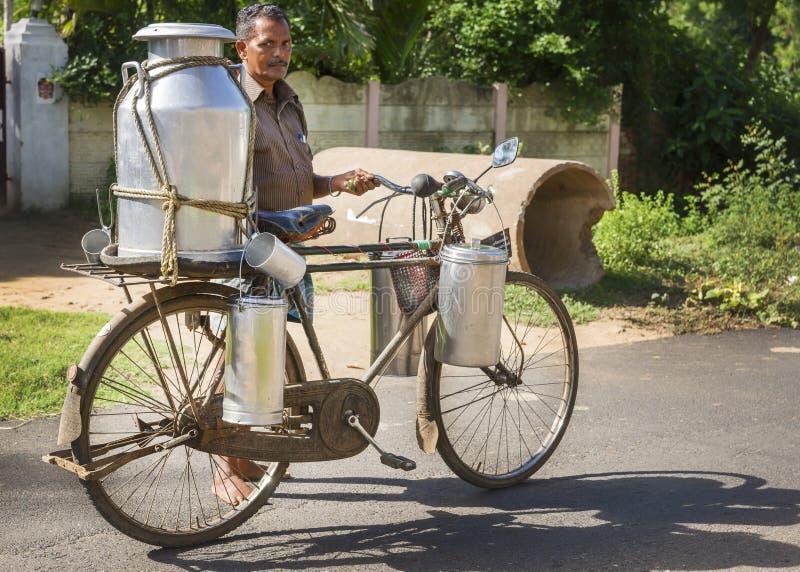 Blikken van de melkboer de dragende melk op zijn fiets royalty-vrije stock afbeelding