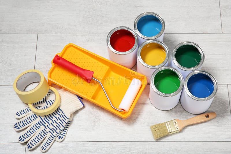 Blikken van verf en decorateurhulpmiddelen stock foto's