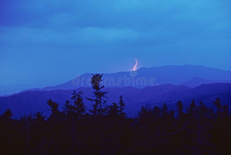 Bliksem bij Schemering in de bergen stock foto's