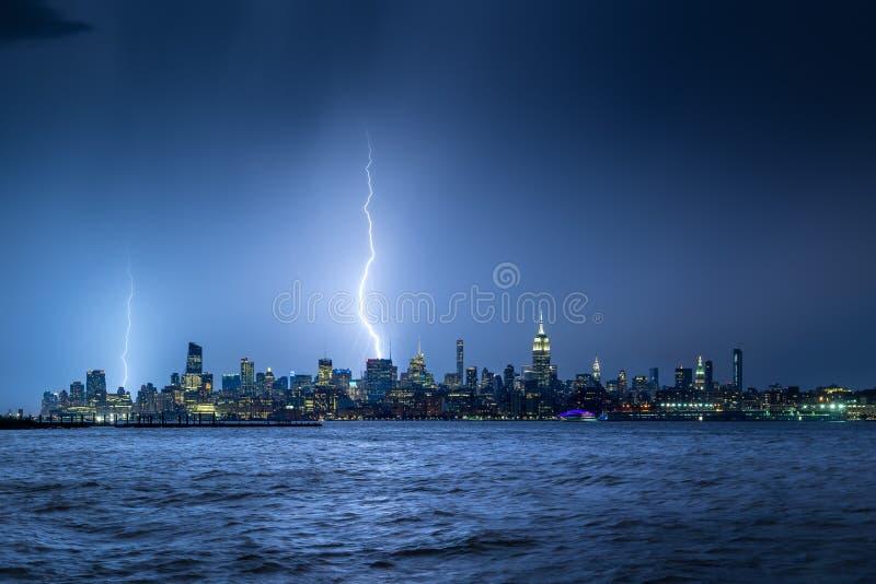 Bliksem die de Stads Uit het stadscentrum wolkenkrabbers slaan van New York bij schemering stock afbeeldingen
