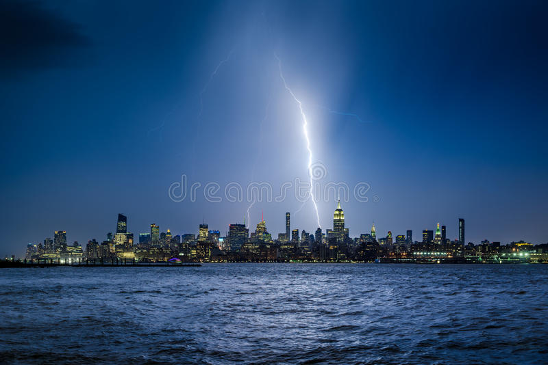 Bliksem die de Stadswolkenkrabbers slaan van New York bij schemering in Uit het stadscentrum Manhattan royalty-vrije stock fotografie