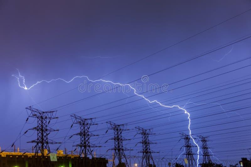 Bliksemstaking op de lijnen van de elektriciteitsmacht en subpost stock afbeelding