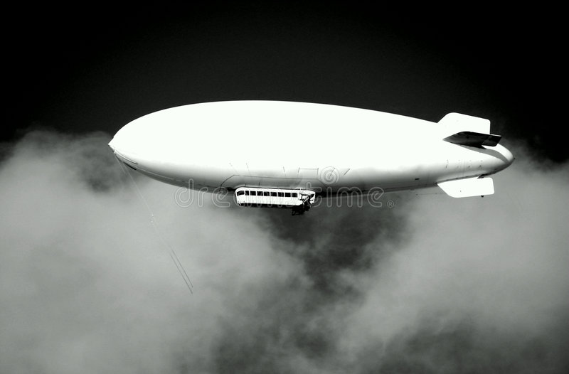 Blimp Dirigible Airship on Dark Stormy Sky. White blimp dirigible airship flying on a menacing and dramatic dark cloudy stormy sky in a storm stock photos