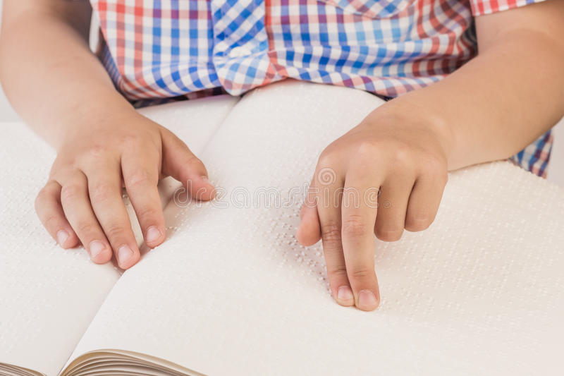The blind boy is reading a book written on Braille. royalty free stock image