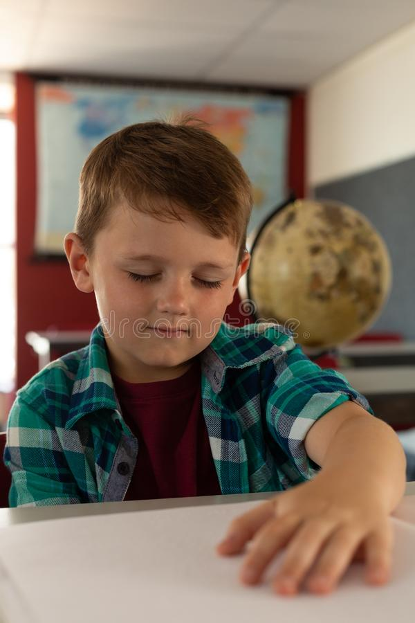 Blind boy reading a braille book at desk in classroom stock photo