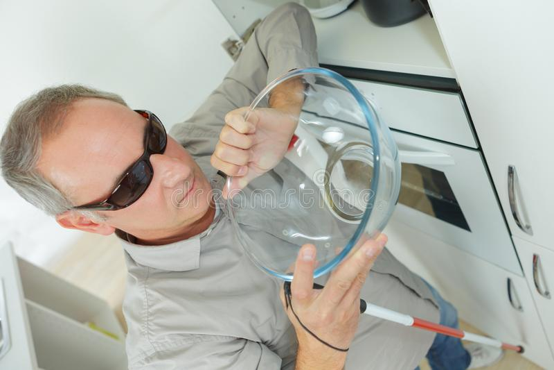 Blind man i kök hemma royaltyfria bilder