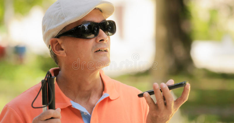 Blind Man Talking With Mobile Phone Disabled Man Speaking. Hispanic blind man with disability. Visually impaired man using Digital Assistant and Ease of Access royalty free stock image