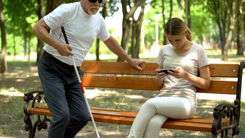 Blind man trying to sit on bench, young lady texting on phone ignoring disabled royalty free stock photos