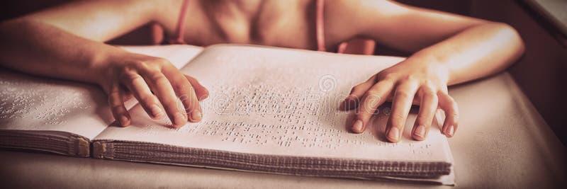 Blind meisje die beide handen gebruiken om braille te lezen stock foto's