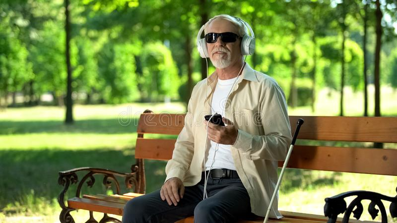 Blind old man wearing earphones listening audiobook, voice message in cellphone. Stock photo royalty free stock image