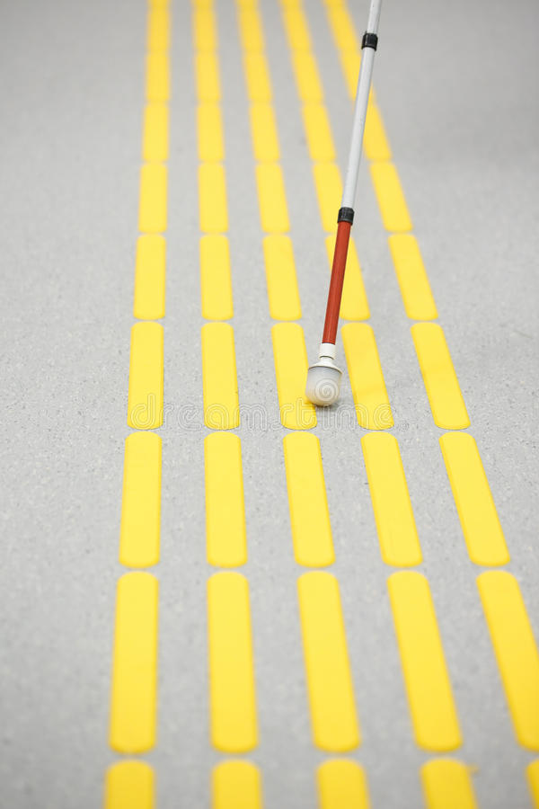 Blind pedestrian walking on tactile paving. Blind pedestrian walking and detecting markings on tactile paving with textured ground surface indicators for blind royalty free stock image