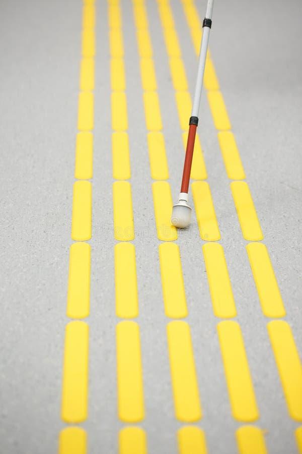 Blind pedestrian walking on tactile paving royalty free stock image
