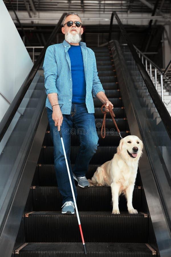 Blind person med den långa rotting- och handbokhunden på rulltrappan royaltyfria foton
