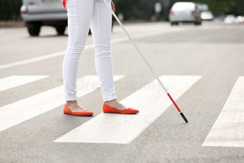 Blind person med den långa rottingkorsningen väg royaltyfria foton