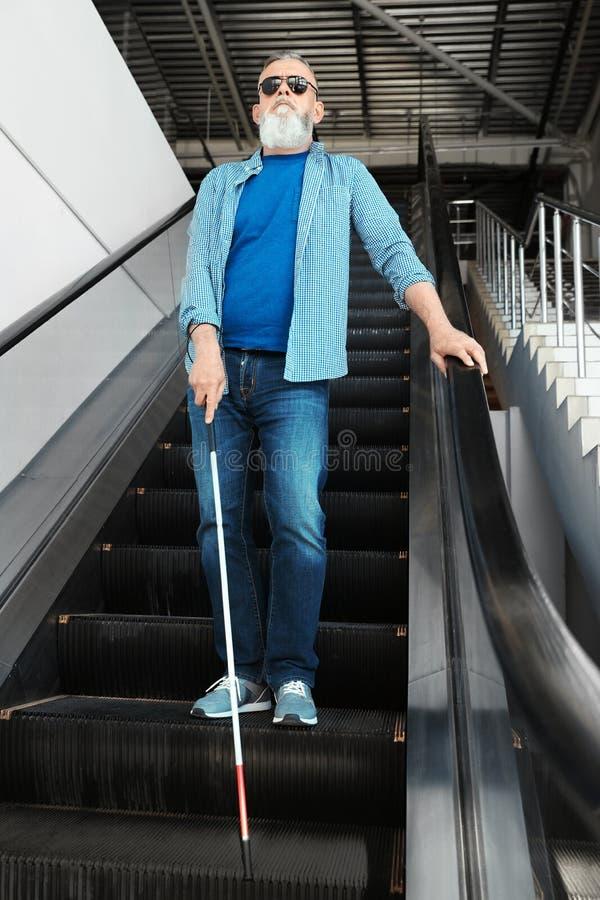 Blind person med den l?nga rottingen p? rulltrappan royaltyfri bild