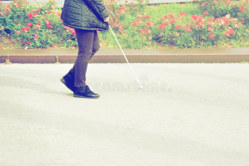 Blind person som går med en pinne som korsar en fot- gångbana tomt kopieringsutrymme arkivbilder