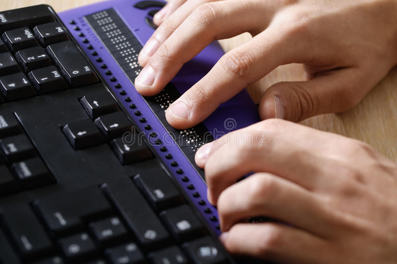 Blind person using computer with braille computer display. And a computer keyboard. Blindness aid, visual impairment, independent life concept royalty free stock photos