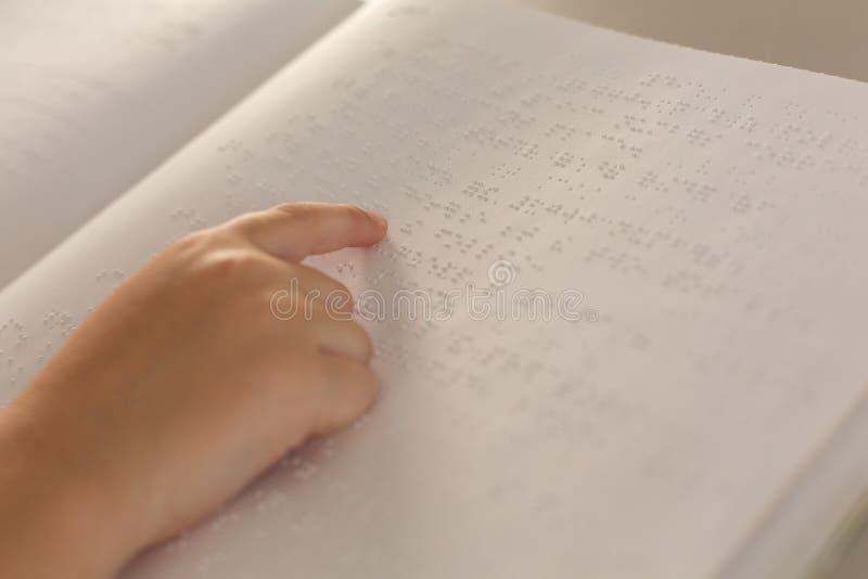 Blind pojkehand som läser en blindskriftbok i klassrum royaltyfri bild