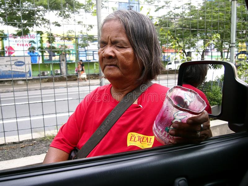 A blind street beggar asks for alms from a car driver. PASIG CITY, PHILIPPINES - OCTOBER 13, 2016: A blind street beggar asks for alms from a car driver royalty free stock photo