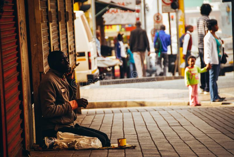 Blind street beggar sitting woman walking past. Johannesburg , Gauteng / South Africa - September 11 2018 : blind man sitting and begging for donations midday stock photos
