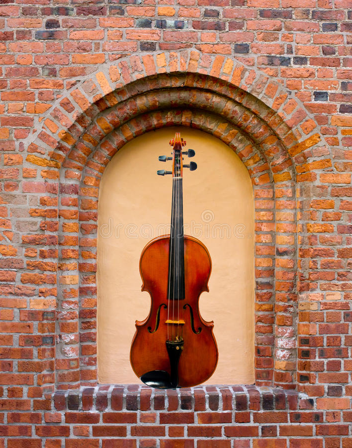 The Blind Windows Violin. The beautiful violin in the blind window in the old brick wall stock images