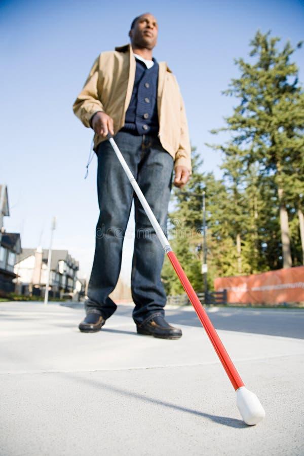 Blinde die een wandelstok met behulp van royalty-vrije stock afbeeldingen