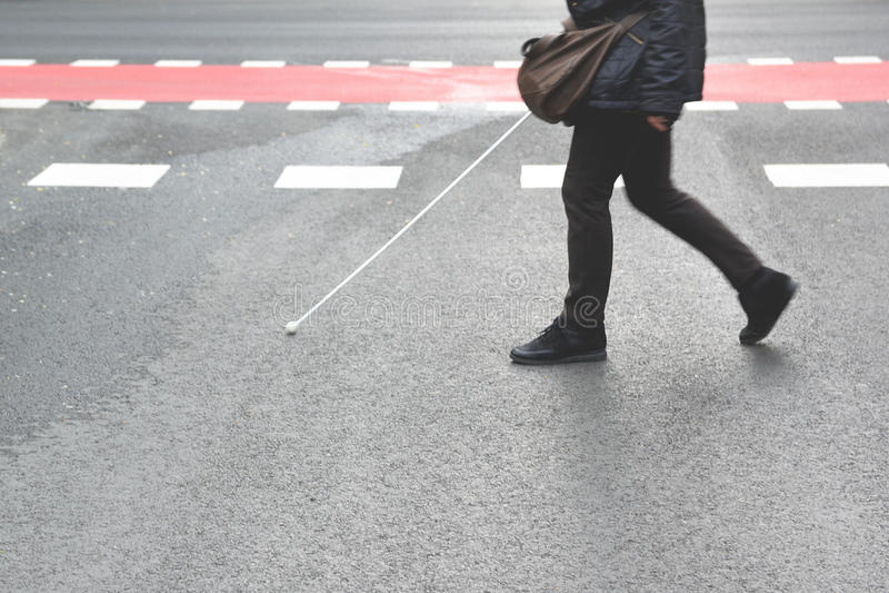 Blinde persoon die met een stok lopen die een voetgang kruisen lege exemplaarruimte stock afbeelding
