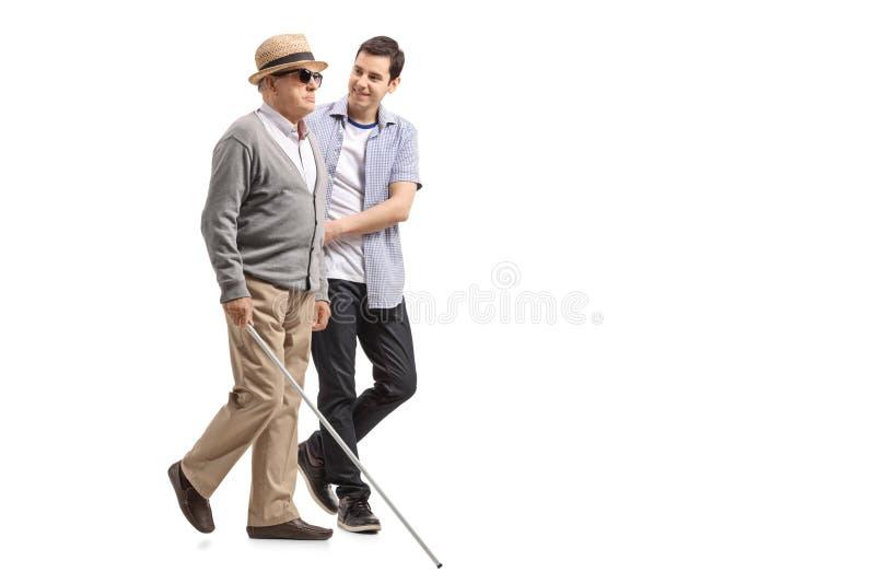 Blinde rijpe mens die met behulp van een jonge mens lopen royalty-vrije stock afbeeldingen