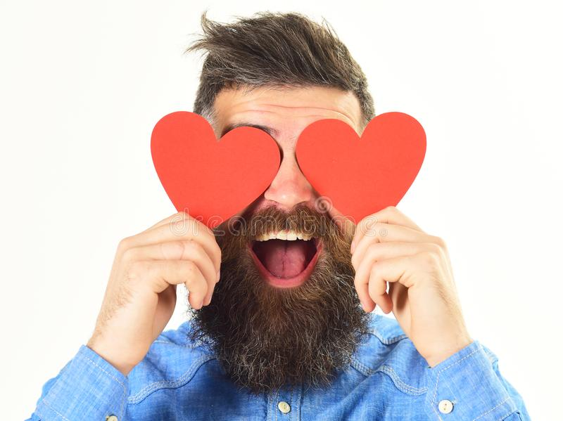 Blinded by love concept. Man with beard holds red hearts. Blinded by love concept. Man with beard holds red paper hearts like eyeglasses. Hipster in love or stock photo