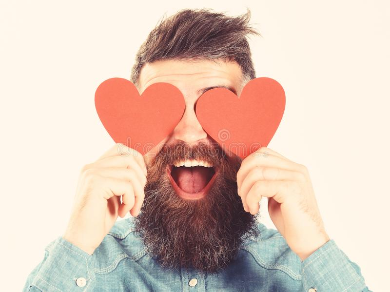 Blinded by love concept. Man with beard holds red hearts. Blinded by love concept. Man with beard holds red paper hearts like eyeglasses. Hipster in love or stock image