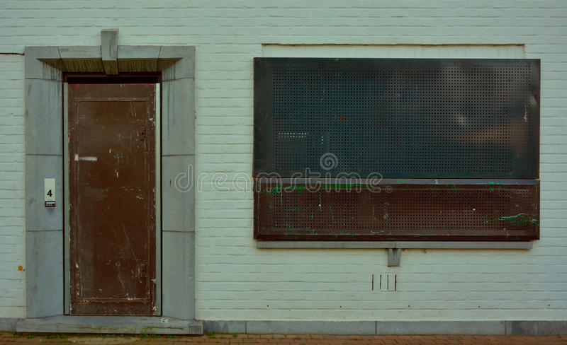 Blinded white urban house. To prevent people to enter a house the doors and windows are blocked by a metal fence, security, reality royalty free stock photography