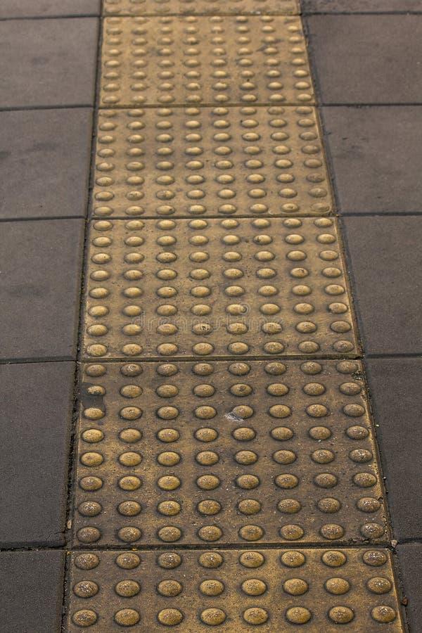 Blindenschrift-Block auf dem Bürgersteig für die Person mit Sehstörungen lizenzfreie stockfotografie