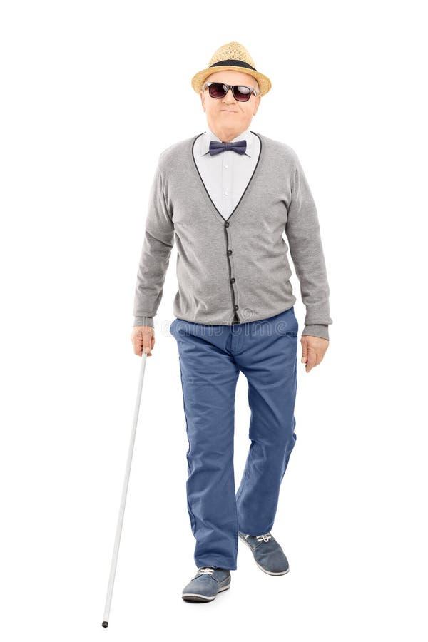 Blinder älterer Herr, der mit einem Stock geht stockbild