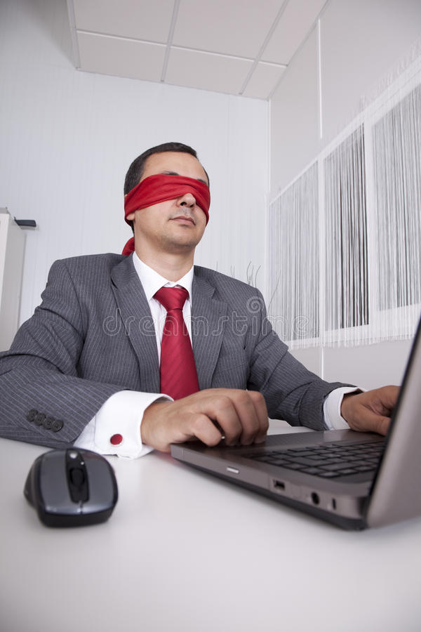Blindfold businessman working with his laptop stock photography
