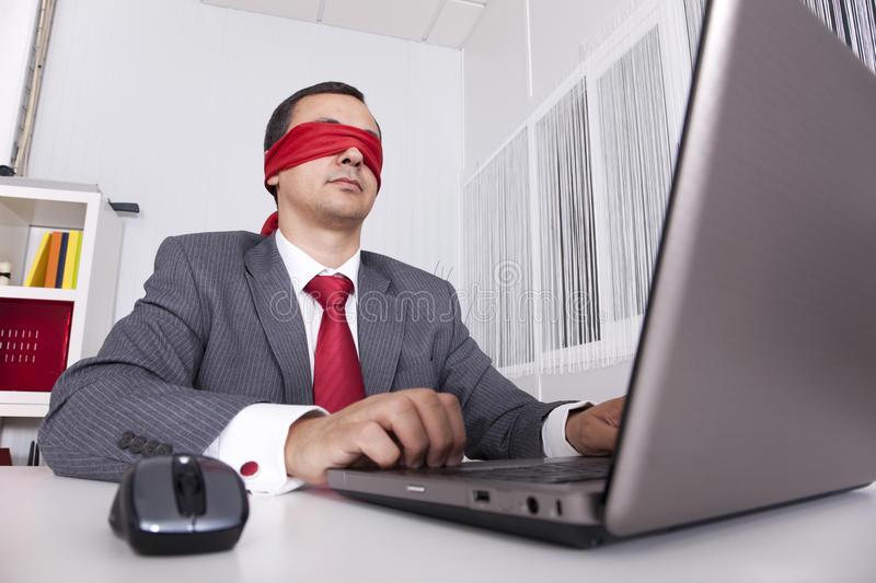 Blindfold businessman working with his laptop stock images