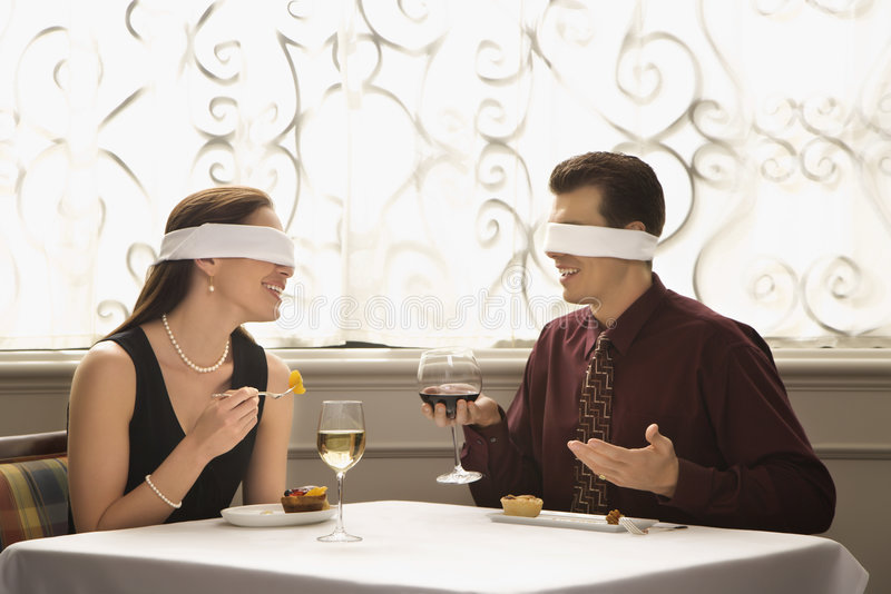 Blindfold couple dining. Mid adult Caucasian couple dining in a restaurant with blindfolds over eyes royalty free stock photography
